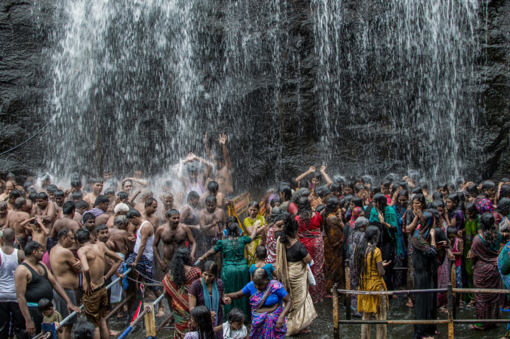 Crowd under a waterfall in Courtlam, India